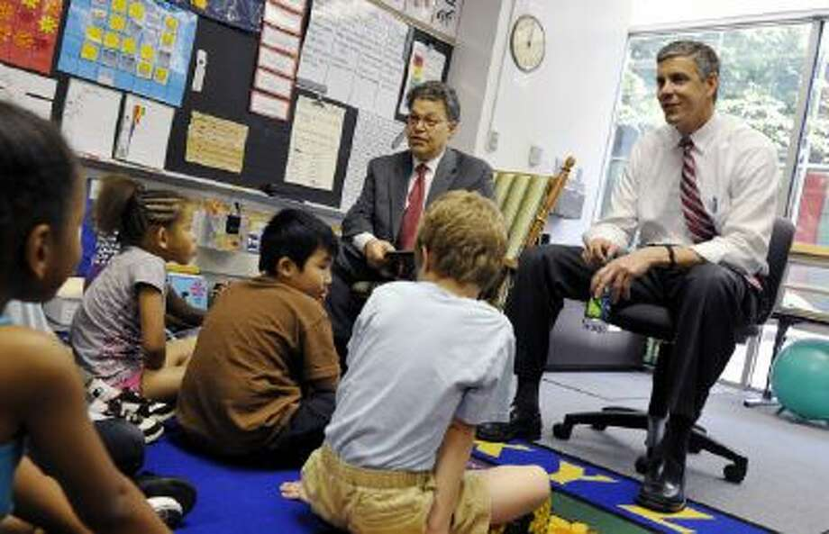 U.S. Education Secretary Arne Duncan, right, and Sen. Al Franken, D-Minn., take questions from first graders in their classroom in May 2011.