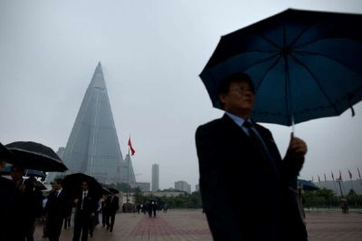 The Ryugyong hotel rises behind a man holding an umbrella in Pyongyang. The North Korean government still has not released any information on its reason for detaining an American citizen last month.
