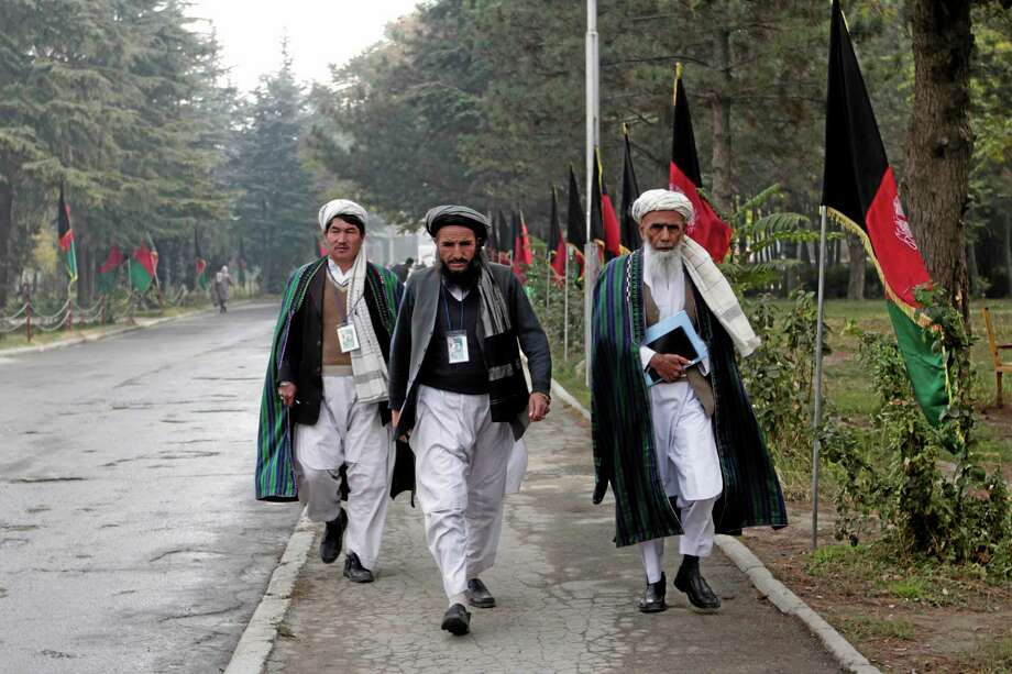Afghan delegates walk on the street on the second day of the Loya Jirga, or the consultative council in Kabul, Afghanistan, Friday, Nov. 22, 2013. Representatives from different groups gather in separate rooms and discuss until meeting again in the council. President Hamid Karzai urged tribal elders Thursday to approve a security pact with Washington that could keep thousands of U.S. troops in Afghanistan until 2024, but he added a wrinkle that he prefers his successor sign the document after elections next April. (AP Photo/Rahmat Gul) Photo: AP / AP