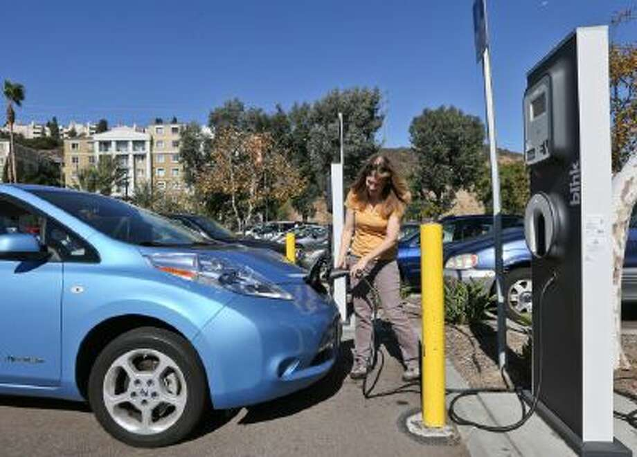 Angie Vorhies plugs in the charging cord to her Nissan Leaf electric vehicle at a mall Nov. 13, 2013, in San Diego.