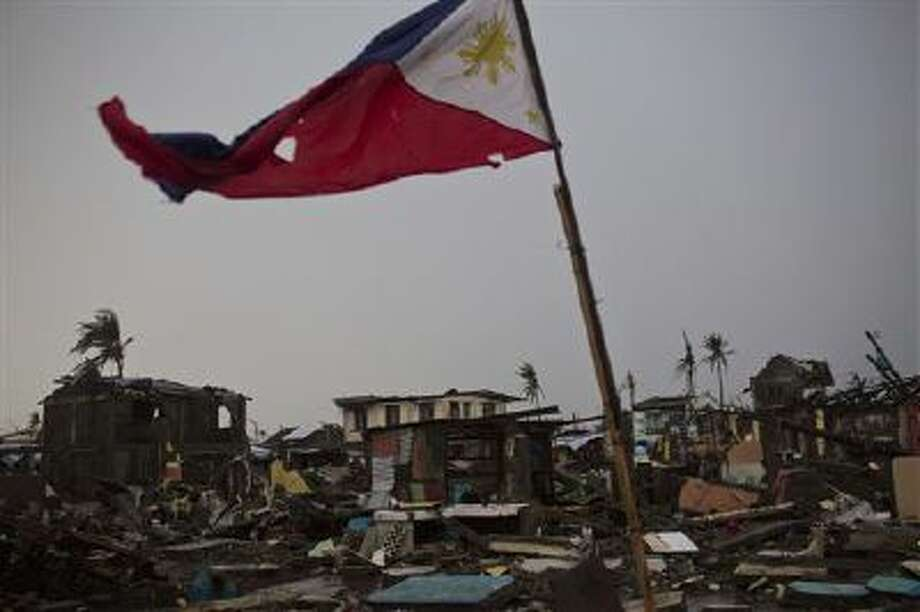 A flag of the Philippines flies over a destroyed neighborhood in Tacloban, Philippines on Friday Nov. 22, 2013. Photo: AP / AP