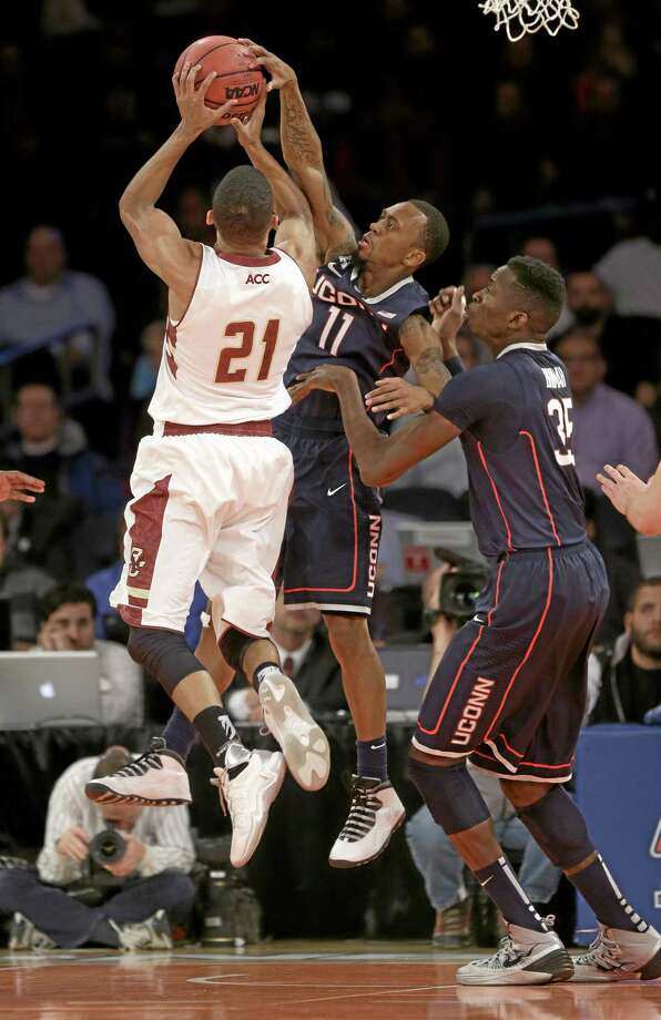 UConn's Ryan Boatright, center, gets his hand on a shot by Boston College's Olivier Hanlan, left, while Amida Brimah looks on during the first half Thursday. Photo: Seth Wenig — The Associated Press  / AP