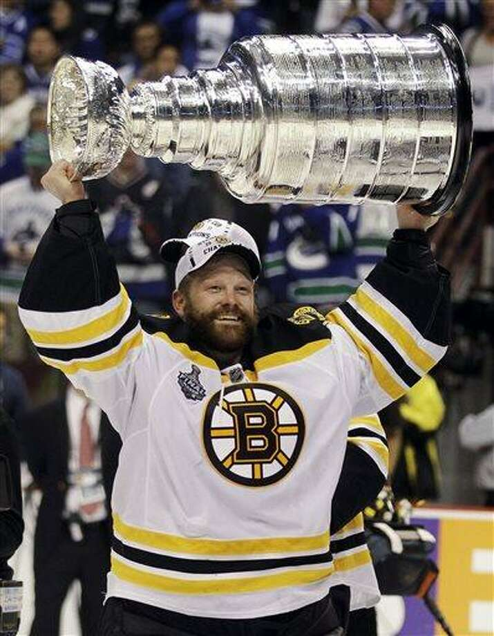 File-This June 15, 2011 file photo shows Boston Bruins goalie Tim Thomas hoisting the Stanley Cup after the Boston Bruins beat the Vancouver Canucks 4-0 during Game 7 of the NHL hockey Stanley Cup Finals in Vancouver, British Columbia.  Thomas is open to resuming his career after taking a season off, his agent says. Bill Zito confirmed Monday, July 1, 2013, that Thomas asked him to explore what teams might be interested in the two-time Vezina Trophy winner once the NHL's free agency period opens Friday.  Zito stressed Thomas is simply assessing his options before determining whether he'll return to play.  (AP Photo/Julie Jacobson, File) Photo: AP / AP