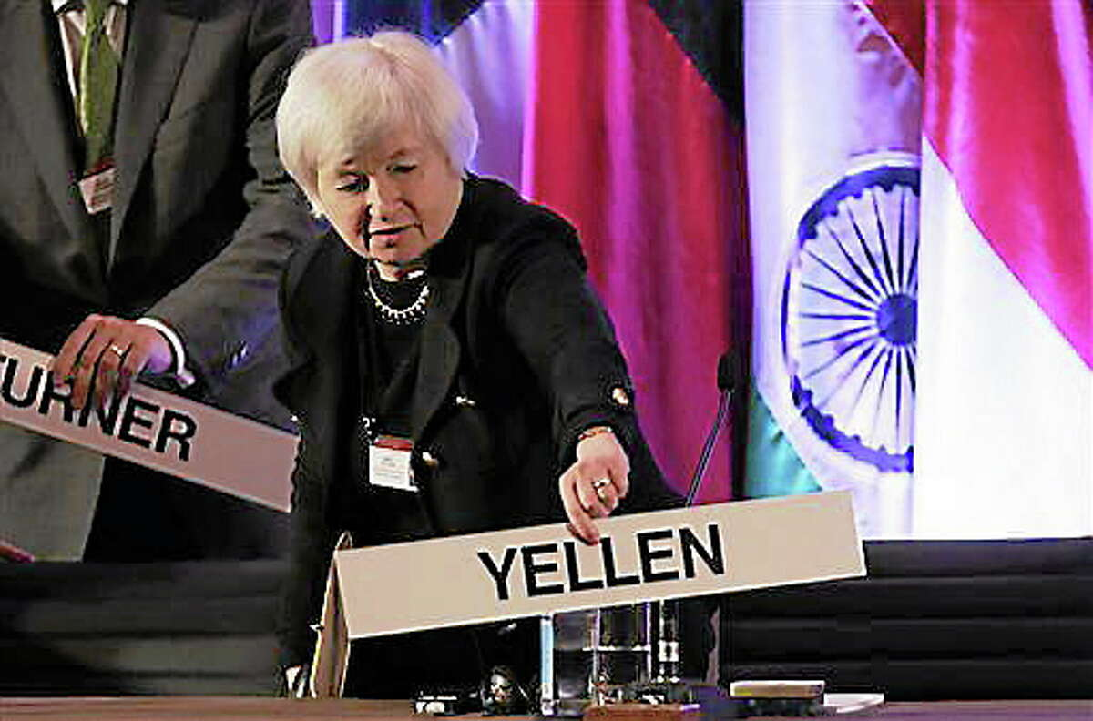 FILE - In this Monday, June 3, 2013, file photo, Janet Yellen, vice chair of the Board of Governors of the Federal Reserve System, places her name plate at her seat at the International Monetary Conference in Shanghai, China. Janet Yellen is expected to face skepticism at a hearing Wednesday, Nov. 13, 2013, on her nomination to lead the Federal Reserve from Republicans who say the Fed's policies may be swelling asset bubbles or raising the risk of high inflation. (AP Photo/Eugene Hoshiko, File)