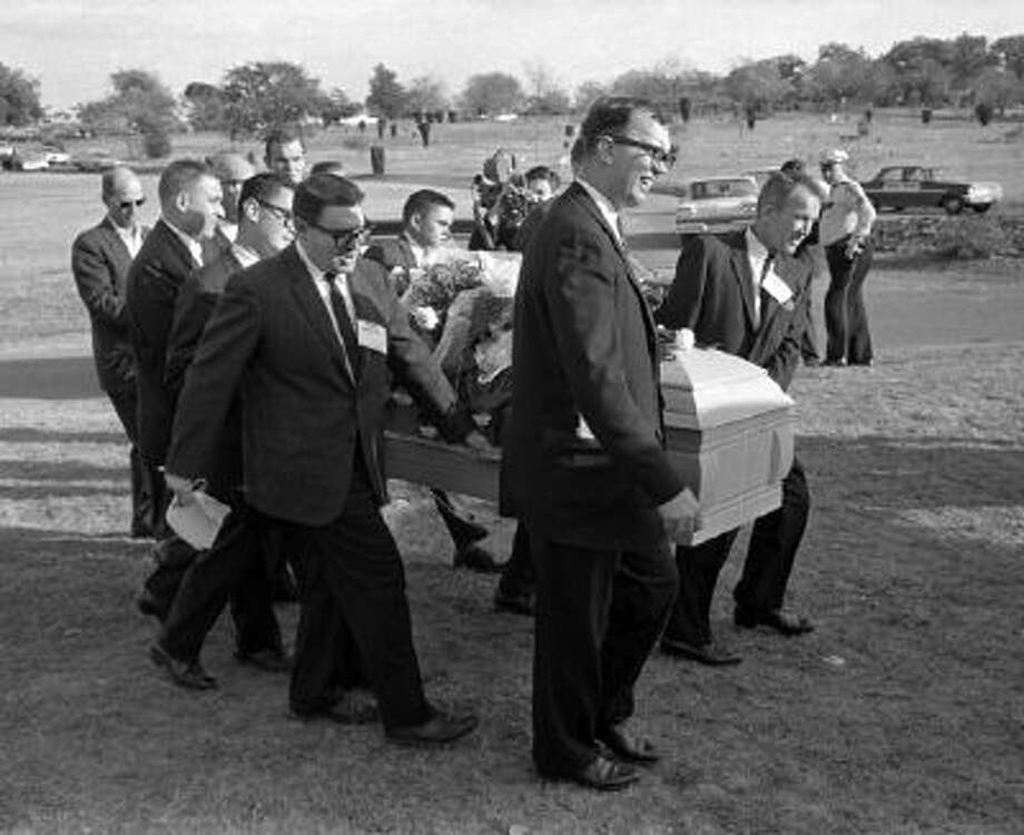 Pallbearers from left end: Jerry Flemmons with crewcut and no glasses. In front of Flemmons are reporters Ed Horn and Mike Cochran. Funeral director Paul J. Groody was among the pallbearers. On the far side of the casket are Jon McConal, rear, and Preston McGraw, front. The pallbearer obscured behind Groody could not be identified.