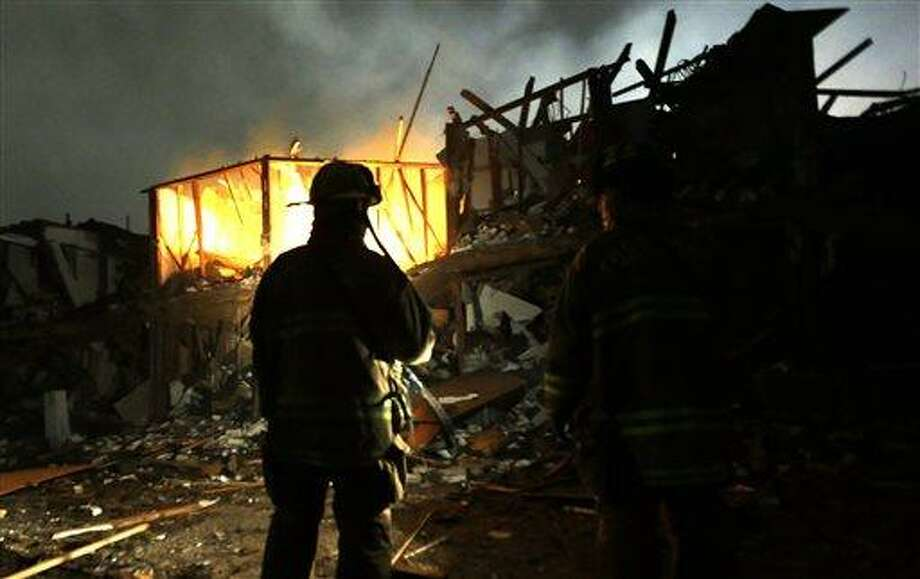 Firefighters use flashlights early Thursday morning, April 18, 2013 to search a destroyed apartment complex near a fertilizer plant that exploded Wednesday night in West, Texas. The massive explosion killed as many as 15 people and injured more than 160, shaking the ground with the strength of a small earthquake and leveling homes and businesses for blocks in every direction. (AP Photo/LM Otero) Photo: AP / AP