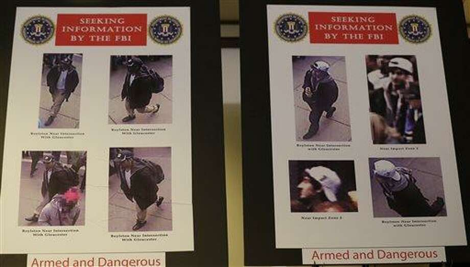 Photos of two suspects sought in the Boston Marathon bombing are displayed during a news conference talking about the investigation of the Boston Marathon explosions, Thursday, April 18, 2013, in Boston. The city continues to cope following Monday's explosions near the finish line of the marathon. (AP Photo/Julio Cortez) Photo: AP / AP