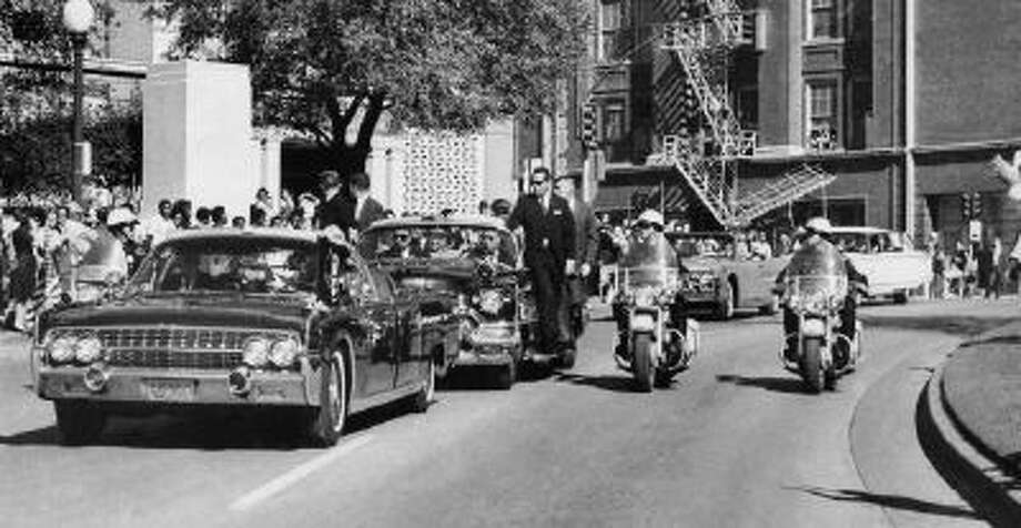 In this Friday, Nov. 22, 1963 file photo, seen through the foreground convertible's windshield, President John F. Kennedy's hand reaches toward his head within seconds of being fatally shot as first lady Jacqueline Kennedy holds his forearm as the motorcade proceeds along Elm Street past the Texas School Book Depository in Dallas.