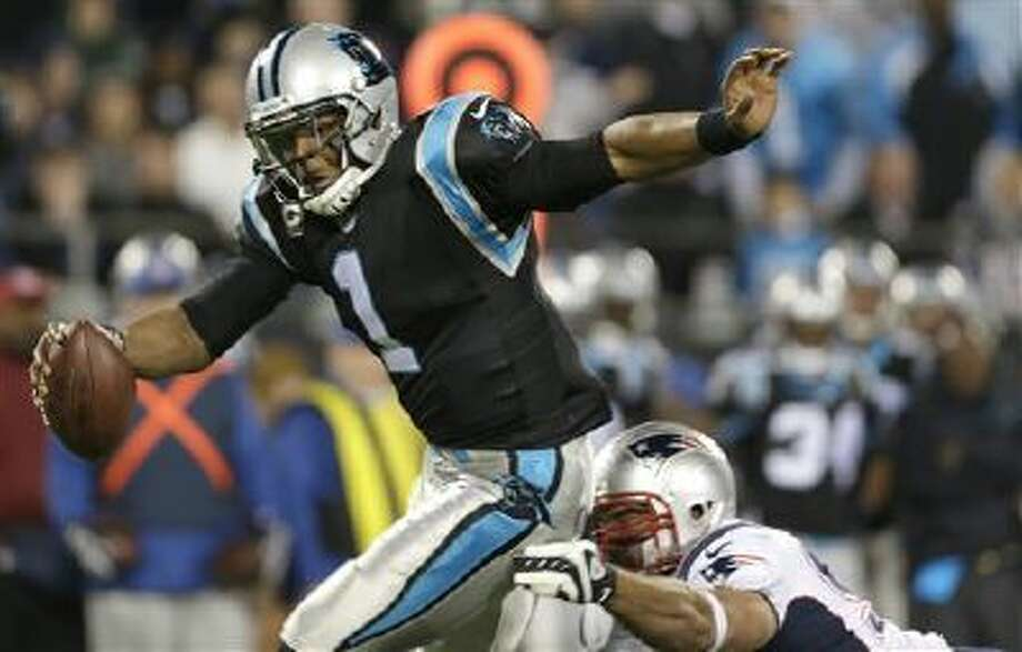 Carolina Panthers' Cam Newton (1) avoids a sack by a New England Patriots defender during the second half of an NFL football game in Charlotte, N.C., Monday, Nov. 18, 2013. Photo: AP / FR170480 AP