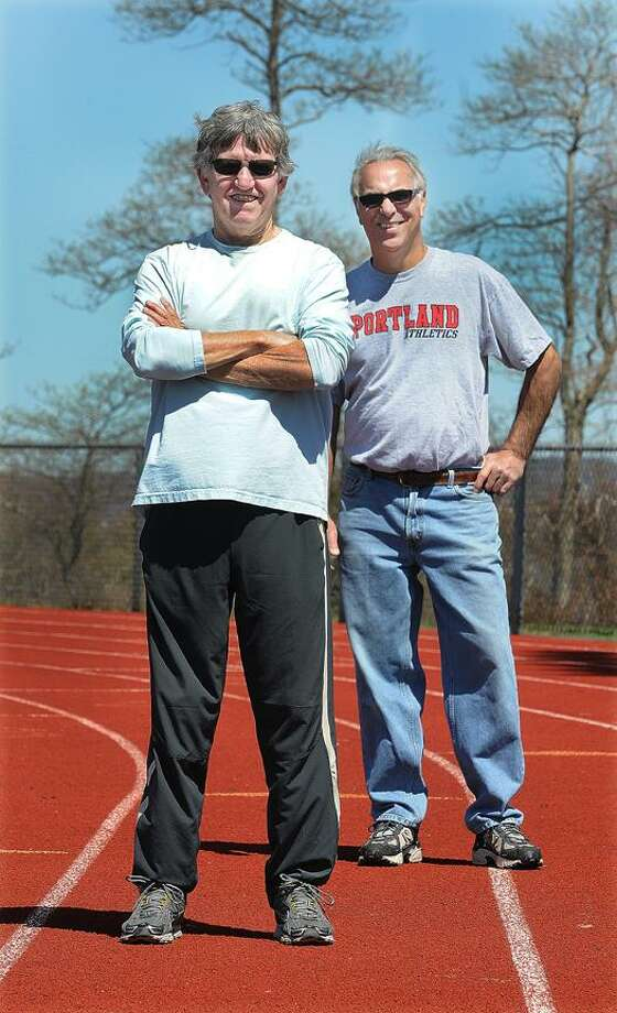 Catherine Avalone/The Middletown Press   Longtime track and field coaches Arnie Liscombe, left, and Nick Chaconis -- two of the major architects in Portland sports history -- stand on the track at Portland High School Wednesday afternoon. / TheMiddletownPress