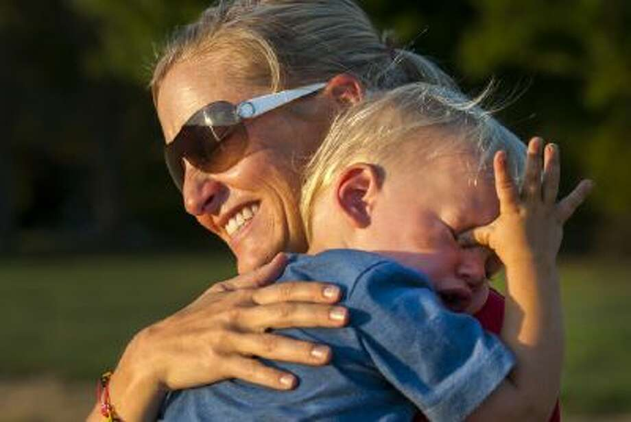 Cathy Reese comforts her son, Braxton, 20 months, as they attend her 7-year-old son's soccer practice.