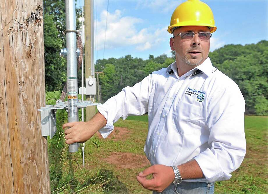 Sean Hayes, owner of Powder Ridge Mountain Park & Resort in Middlefield flips the switch to return power to the ski area Friday afternoon. Workers renovating the resort have spent the last nine months using generators for power. Photo: Journal Register Co. / TheMiddletownPress