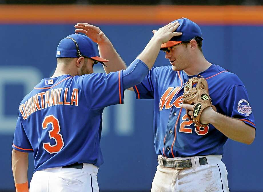 The Mets' Daniel Murphy, right, and Omar Quintanilla celebrate after their 11-3 win against the Phillies at Citi Field on Thursday. Photo: Seth Wenig — The Associated Press  / AP
