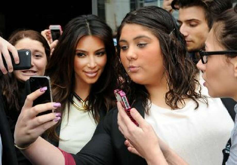 "Kim Kardashian, left, take part in a selfie with a fan in Melbourne, Australia. ""Selfie"" the smartphone self-portrait has been declared word of the year for 2013 by Britain's Oxford University Press."