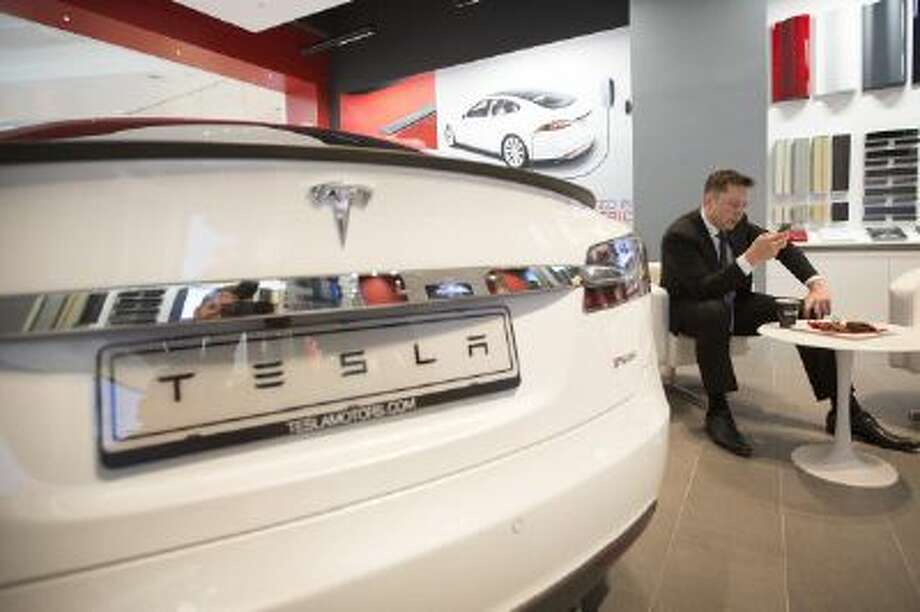 Elon Musk, billionaire, co-founder and chief executive officer of Tesla Motors Inc., checks a mobile device as a Tesla Model S automobile sits on display in the Tesla store at Westfield Stratford City retail complex in London, U.K., on Thursday, Oct. 24, 2013. Photo: Bloomberg Via Getty Images / 2013 Bloomberg