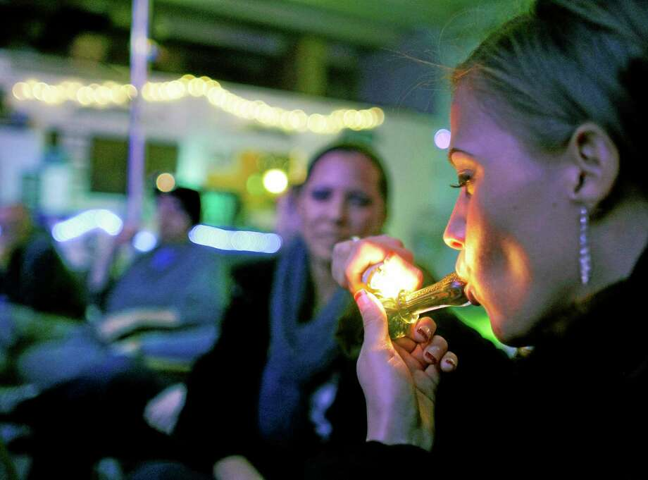FILE - In this in Dec. 31, 2012 file photo, Rachel Schaefer of Denver smokes marijuana on the official opening night of Club 64, a marijuana-specific social club, where a New Year's Eve party was held,  in Denver. According to new guidance being issued Thursday, Aug. 29, 2013 to federal prosecutors across the country, the federal government will not make it a priority to block marijuana legalization in Colorado or Washington or close down recreational marijuana stores, so long as the stores abide by state regulations. (AP Photo/Brennan Linsley) Photo: AP / AP