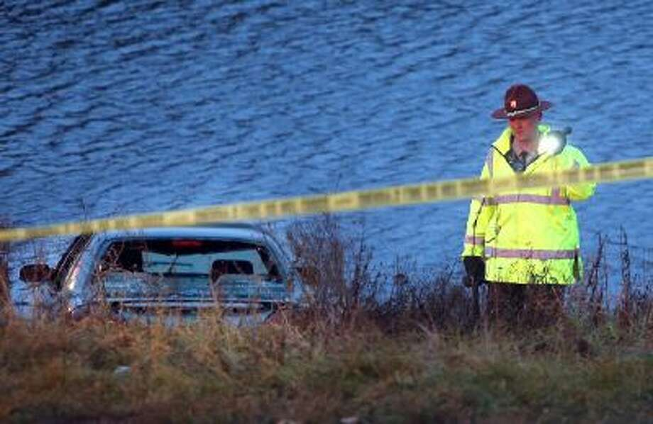 A police officer investigates the scene where six people were rescued after their car went into a holding pond near a highway exit ramp Thursday, Nov. 21, 2013, in St. Louis Park, Minn.