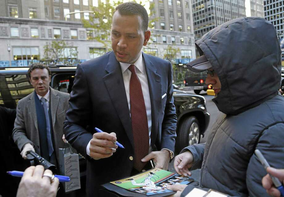 Alex Rodriguez signs autographs as he arrives at Major League Baseball headquarters in New York on Tuesday. Photo: Seth Wenig — The Associated Press  / AP