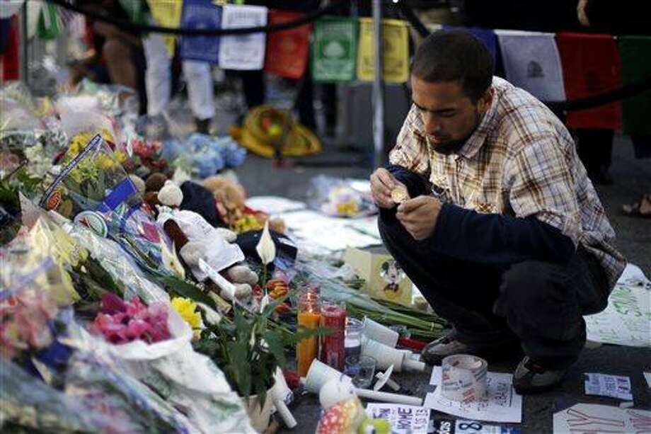 Richard Maldonado lights a candle at a makeshift memorial on Boylston Street near the finish line of Monday's Boston Marathon explosions, which killed at least three and injured more than 140,  Wednesday, April 17, 2013, in Boston. (AP Photo/Matt Rourke) Photo: AP / AP