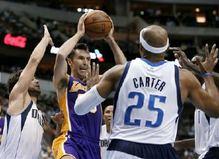 Los Angeles Lakers guard Steve Nash, center, goes up to pass from beneath the basket as Dallas Mavericks' Jose Calderon, left, of Spain, and Vince Carter (25) defend in the first half of an NBA basketball game, Tuesday, Nov. 5, 2013, in Dallas. Photo: AP / AP
