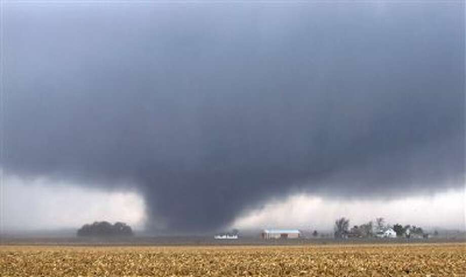 A tornado moves northeast Sunday, two miles west of Flatville, Ill. The tornado damaged many farm buildings and homes on its way to Gifford, Ill., where scores of houses were devastated. Photo: AP / News-Gazette