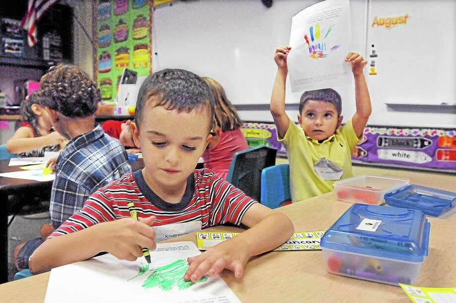 "Cromwell kindergartener Cole Leavitt raises his paper to show his teacher his completed work as Brody Duncan continues to color a picture of his hand after their teacher Darcy Pedersen read ""The Kissing Hand"" by Audrey Penn on the first day of school at Edna C. Stevens Elementary School Wednesday afternoon. Catherine Avalone - The Middletown Press Photo: Journal Register Co. / TheMiddletownPress"
