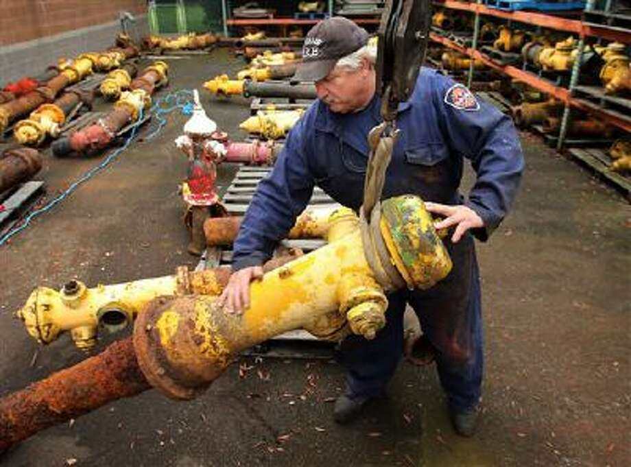 Don Gleason, emergency equipment technician with the Eugene Fire Department in Eugene, Ore. unloads the last fire hydrant that was made in Eugene that was until recently still in service into a storage yard Wednesday, Nov. 13, 2013. Photo: AP / The Register-Guard