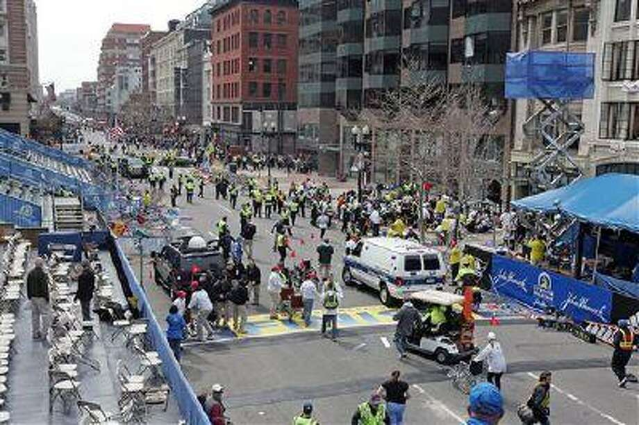 People react to an explosion at the 2013 Boston Marathon in Boston, Monday. Two explosions shattered the euphoria of the Boston Marathon finish line on Monday, sending authorities out on the course to carry off the injured while the stragglers were rerouted away from the smoking site of the blasts. Photo: AP / Boston Herald