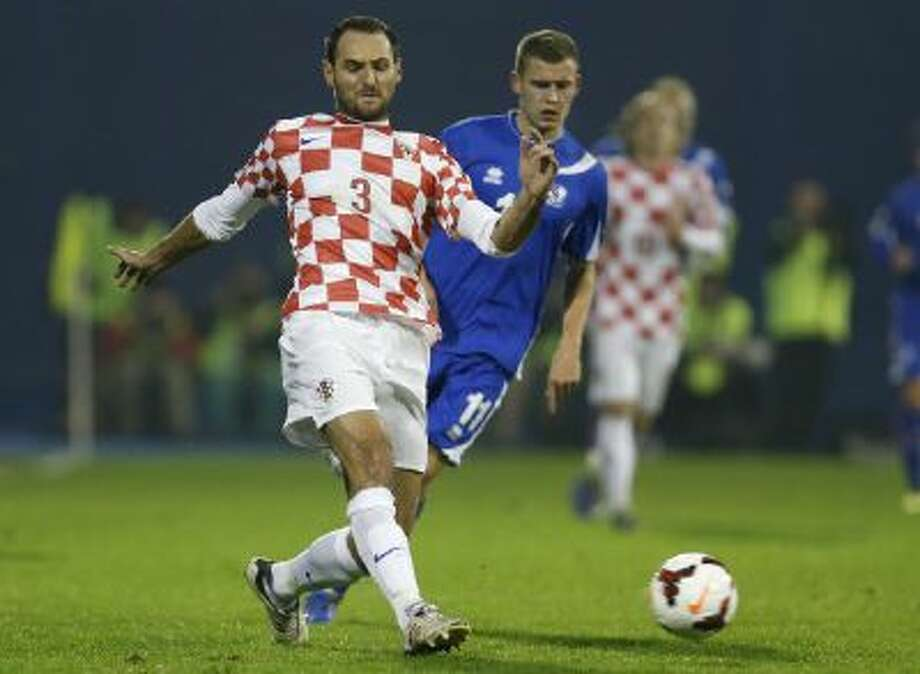 Croatia's defender Josip Simunic, left, is challenged by Iceland's Alfred Finnbogason during their World Cup qualifying playoff second leg soccer match against Iceland, in Zagreb, Croatia. Croatia's World Cup qualification celebrations have been marred by apparent pro-Nazi chants by fans and defender Josip Simunic. Croatia qualified for the World Cup with a 2-0 win over Iceland on Tuesday.