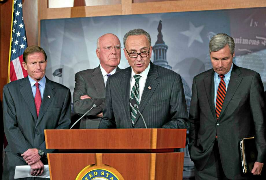 Sen. Chuck Schumer, D-N.Y., center, speaks to reporters after Senate Republicans derailed President Barack Obama's selection of Georgetown University law professor Cornelia Pillard to fill one of three vacancies on the U.S. Court of Appeals for the District of Columbia Circuit, at the Capitol in Washington, Tuesday, Nov. 12, 2013, as from left, Sen. Richard Blumenthal, D-Conn., Senate Judiciary Committee Chairman Patrick Leahy, D-Vt., amd Sen. Sheldon Whitehouse, D-R.I., listen. Democrats used the vote to assail Republicans for opposing female nominees to the D.C. circuit. (AP Photo/J. Scott Applewhite) Photo: AP / AP