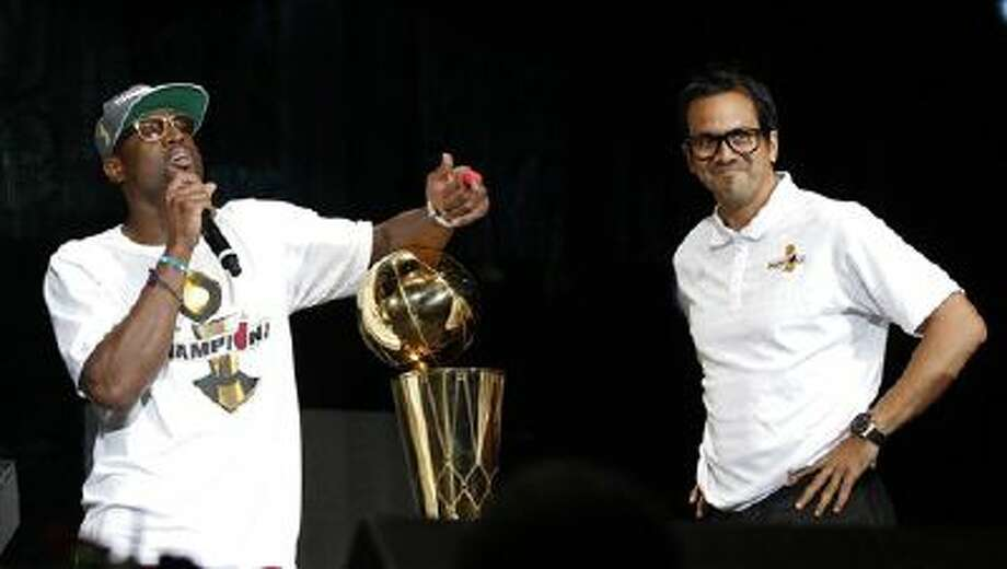 Miami Heat's Dwyane Wade talks to the fans as head coach Erik Spoelstra smiles during a public celebration of the NBA Champions at the arena in Miami, Monday, June 25, 2012. Photo: ASSOCIATED PRESS / AP2012