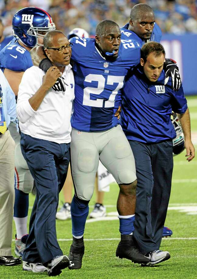 Trainers carry New York Giants safety Stevie Brown off the field after he was injured on a play during the first half of a preseason game against the New York Jets on Saturday in East Rutherford, N.J. Photo: Bill Kostroun — The Associated Press  / FR51951 AP
