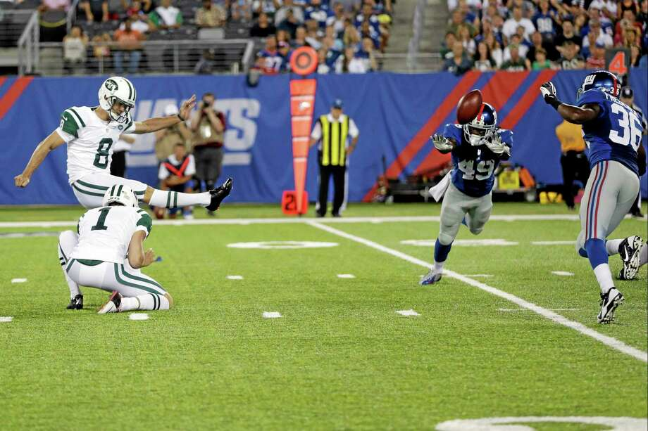 New York Jets place kicker Billy Cundiff kicks a field goal past the New York Giants' Junior Mertile (49) to win the game during overtime of a preseason game on Saturday in East Rutherford N.J. The Jets won the game 24-21. Photo: Julio Cortez — The Associated Press  / AP