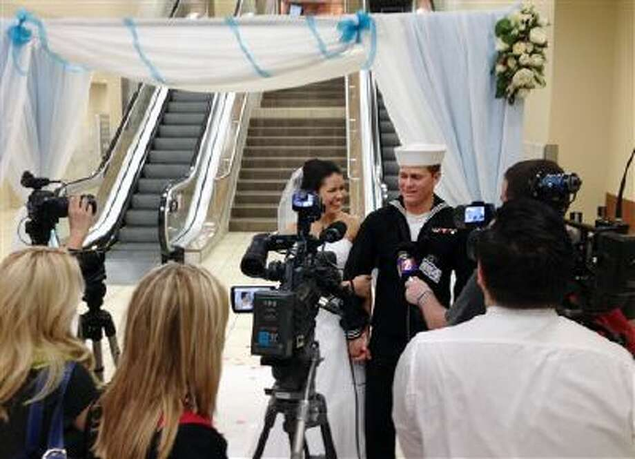Navy seaman Dylan Ruffer and his fiancee, Madison Meinhardt, both from Chester, Calif., talk to news reporters Tuesday after getting married in front of the arrivals escalators at the Reno-Tahoe International Airport in Reno, Nev. Ruffer married his high school sweetheart just moments after returning from an 11-month deployment off the coast of war-torn Syria. More than 200 invited guests, passengers and others looked on. Photo: AP / Heidi Jared