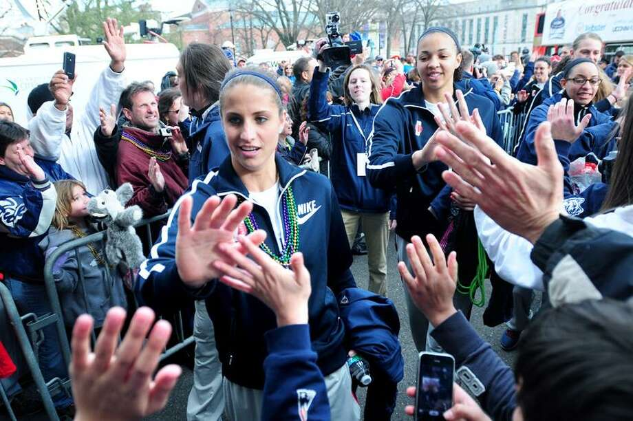 UCONN's Caroline Doty (left) followed by teammate Kiah Stokes high fives fans after a parade through downtown Hartford Sunday. Photo by Arnold Gold/New Haven Register