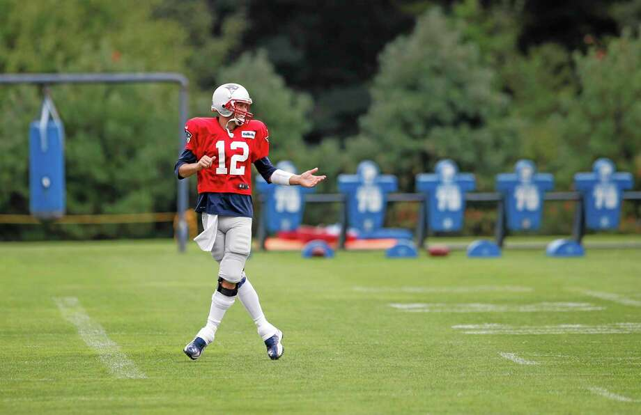 New England Patriots quarterback Tom Brady laughs as he warms up during team football practice in Foxborough, Mass., on Monday. Photo: Elise Amendola — The Associated Press  / AP