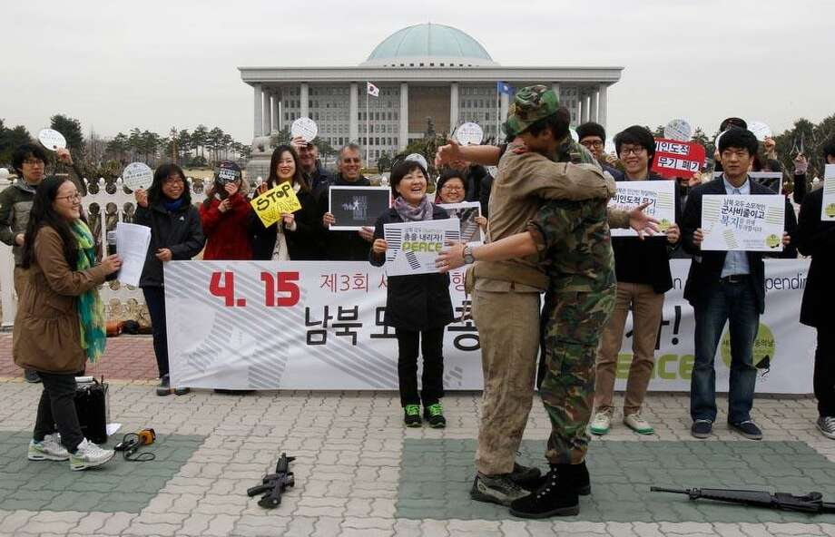 Anti-war activists wearing military clothes of a North, left, and South Korea hug each other during a rally to mark Global Day of Action on Military Spending in front of the National Assembly in Seoul, South Korea, Monday, April 15, 2013. They demanded peaceful unification of the Korean peninsula. Elsewhere in the region, however, the focus remained on the threat of a missile launch by the North as U.S. Secretary of State John Kerry wrapped up a tour to coordinate Washington's response with Beijing, North Korea's most important ally, as well as Seoul and Tokyo. (AP Photo/Ahn Young-joon) Photo: AP / AP