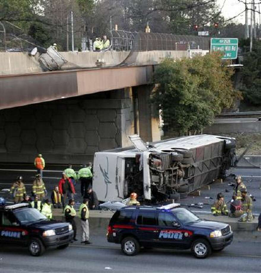This March 2, 2007 file photo shows a charter bus carrying the Bluffton University baseball team from Ohio after it plunged off a highway ramp in Atlanta and slammed into the I-75 pavement below. Federal regulators say they will require that new tour buses and buses that carry passengers on scheduled routes between cities be equipped with seat belts. Photo: AP / AP