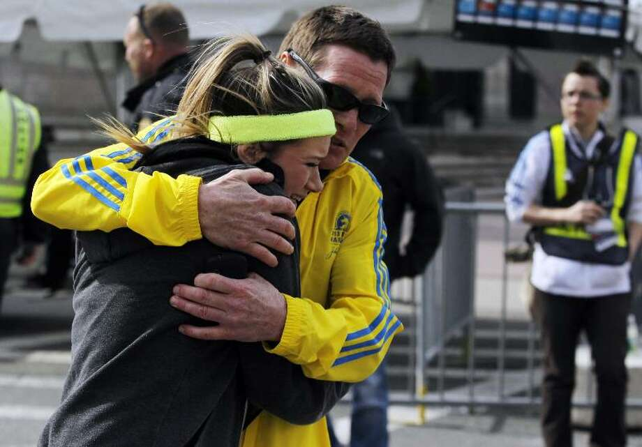 A woman is comforted by a man near a triage tent after explosions went off at the 117th Boston Marathon in Boston, Massachusetts. (Jessica Rinaldi/Reuters)