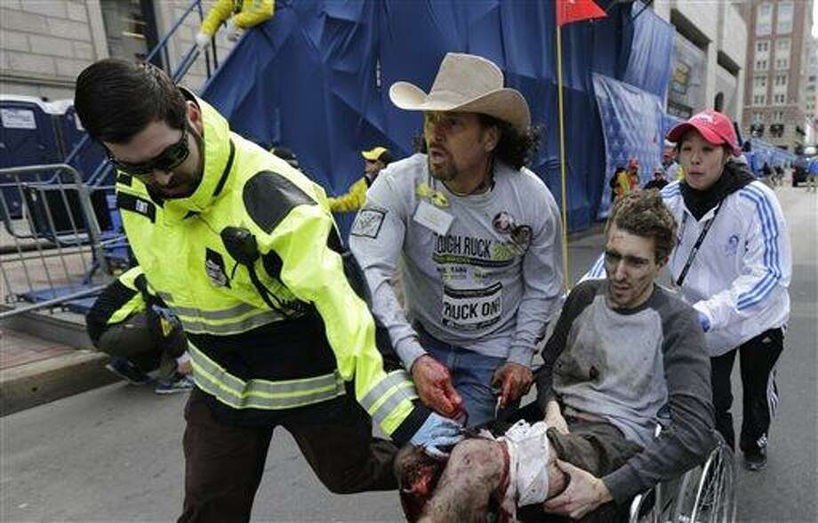 Medical responders run an injured man past the finish line the 2013 Boston Marathon following an explosion in Boston, Monday, April 15, 2013. Two explosions shattered the euphoria of the Boston Marathon finish line on Monday, sending authorities out on the course to carry off the injured while the stragglers were rerouted away from the smoking site of the blasts. (AP Photo/Charles Krupa) Photo: AP / AP
