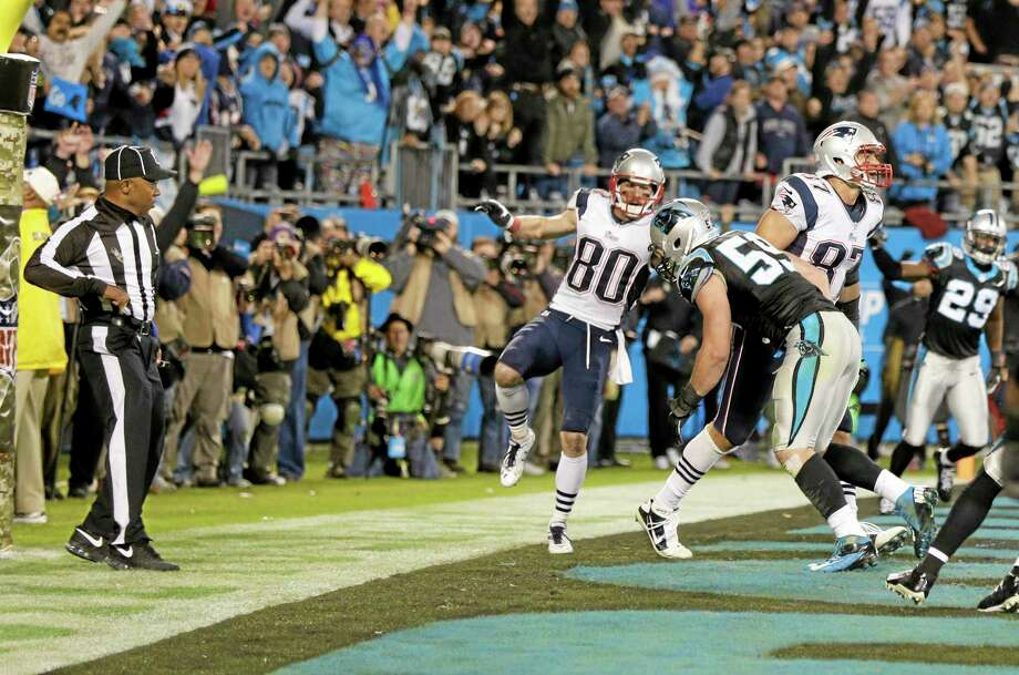 An official, left, reaches for his flag as Carolina Panthers linebacker Luke Kuechly (59) hits New England Patriots tight end Rob Gronkowski (87) in the end zone on the last play of Monday night's game in Charlotte, N.C. The officials ruled no penalty on the play. Photo: Chuck Burton — The Associated Press  / AP