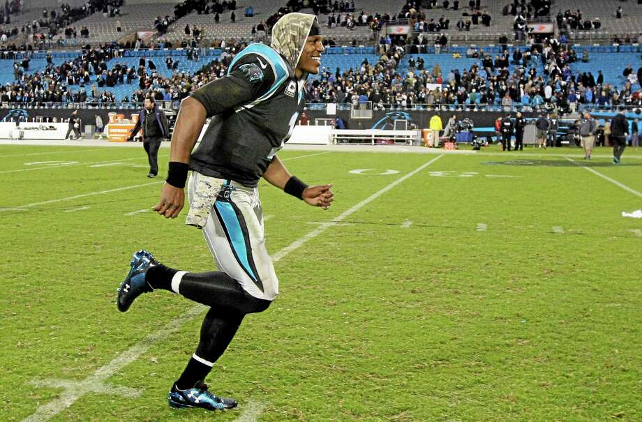 Panthers quarterback Cam Newton smiles as he runs off the field following Carolina's 24-20 win over the New England Patriots on Monday night in Charlotte, N.C. Photo: Gerry Broome — The Associated Press  / AP