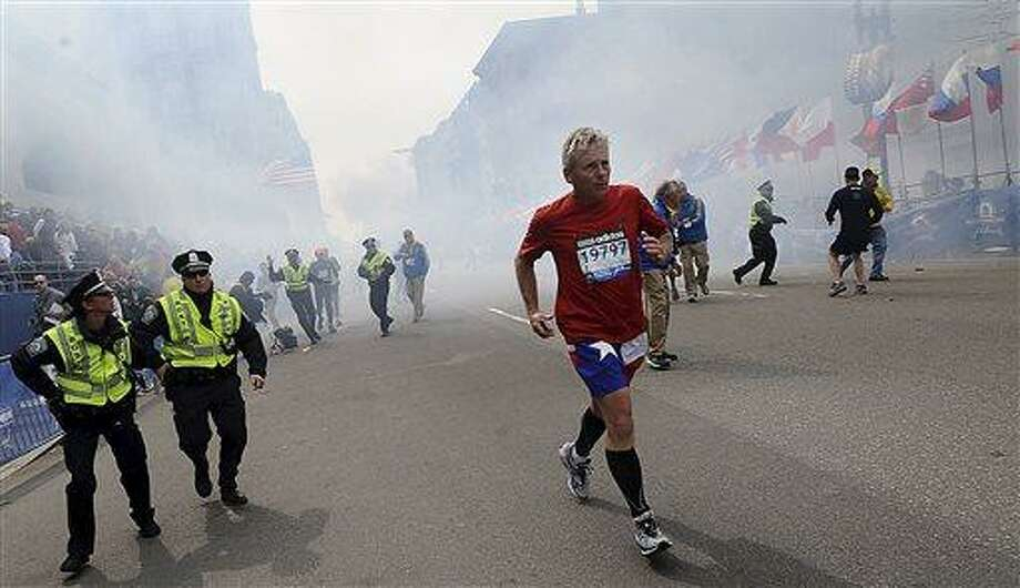 A Boston Marathon competitor and Boston police run from the area of an explosion near the finish line in Boston, Monday, April 15, 2013. (AP Photo/MetroWest Daily News, Ken McGagh)  MANDATORY CREDIT Photo: AP / MetroWest Daily News