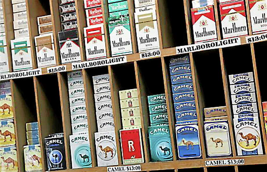 In this March 18, 2013 file photo cigarette packs are displayed for sale at a convenience store in New York. No one under 21 would be able to buy cigarettes in New York City under a proposal unveiled Monday, April 22, 2013 to make the city the most populous place in America to set the minimum age that high. (AP Photo/Mark Lennihan, file) Photo: AP / AP