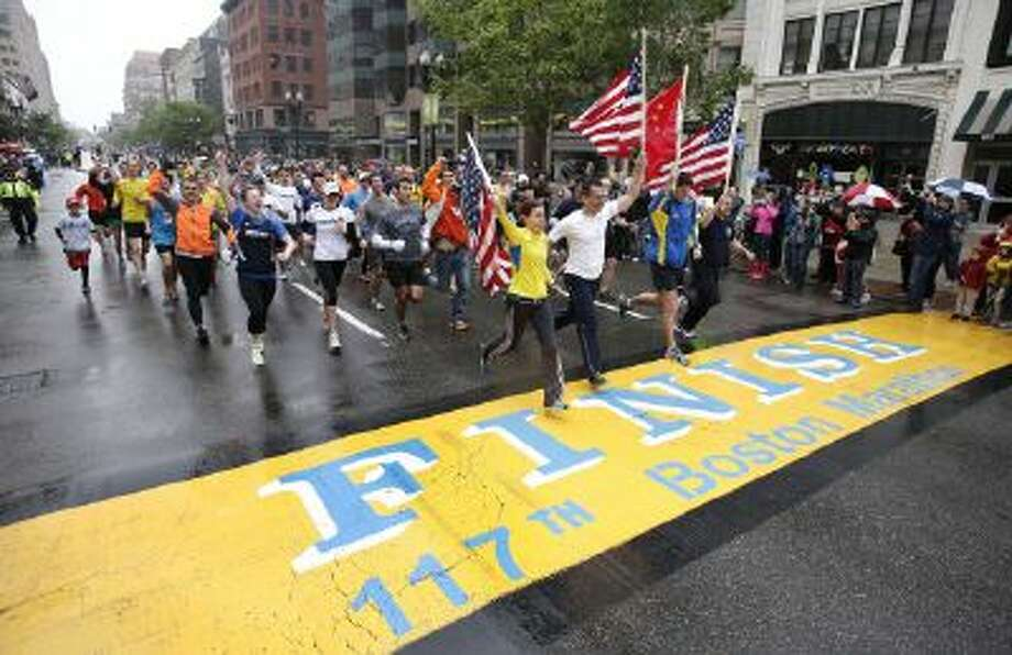 Runners who were unable to finish the Boston Marathon on April 15 because of the bombings cross the finish line on Boylston Street after the city allowed them to finish the last mile of the race in Boston on May 25.