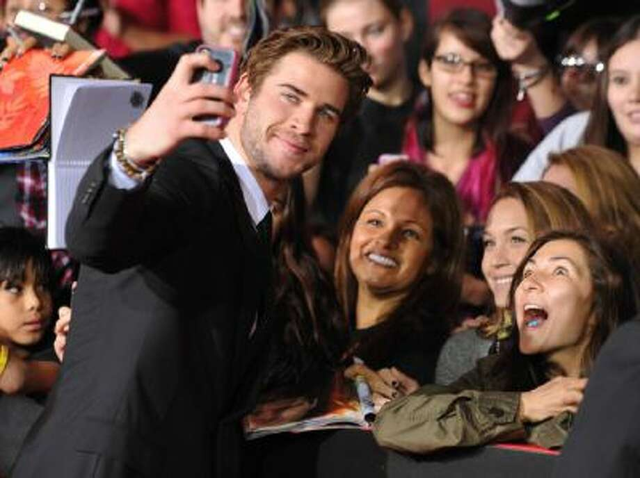 "Liam Hemsworth poses for a photo with fans as he arrives at the Los Angeles premiere of ""The Hunger Games: Catching Fire"" at Nokia Theatre LA Live on Nov. 18, 2013."