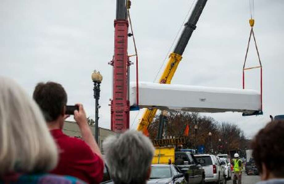Bystanders watch and take pictures as an historic rail car is hoisted by two cranes Nov. 17, 2013 at the construction site of the National Museum of African American History and Culture in Washington.