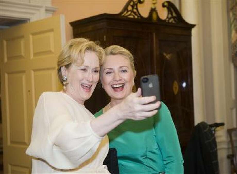 In this Saturday, Dec. 1, 2012, file photo Actress Meryl Streep uses her iPhone to take a photo of her and Secretary of State Hillary Rodham Clinton following the State Department Dinner for the Kennedy Center Honors gala at the State Department in Washington. Photo: AP / FR33460 AP