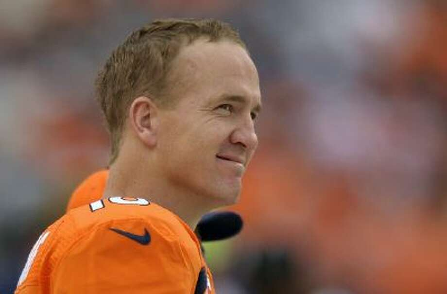 In this Sept. 29, 2013 file photo, Denver Broncos quarterback Peyton Manning watches play from the sidelines against the Philadelphia Eagles in the fourth quarter an NFL football game, in Denver. Manning returns to Indianapolis on Sunday, Oct. 20, 2013, a better quarterback than the one who left.