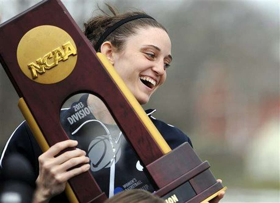 Connecticut's Kelly Faris holds the championship trophy during a parade through campus honoring the team's win in the women's NCAA Final Four college basketball championship in Storrs, Conn., Wednesday, April 10, 2013. (AP Photo/Jessica Hill) Photo: ASSOCIATED PRESS / AP2013